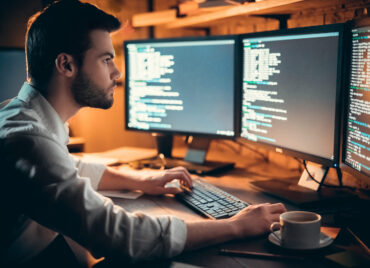 Focused young developer coding late in office writing script shown on computer monitors, serious handsome coder programmer hacker programming developing software applications working alone at night